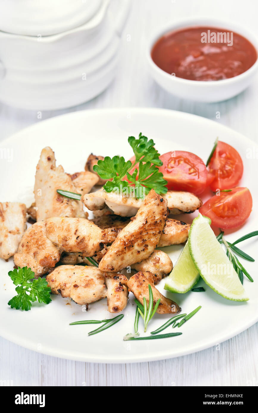 Roast chicken fillet sliced and vegetables on white plate - Stock Image