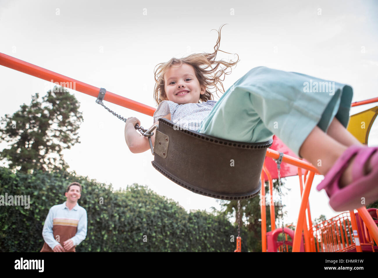 Caucasian father pushing daughter on swing Stock Photo