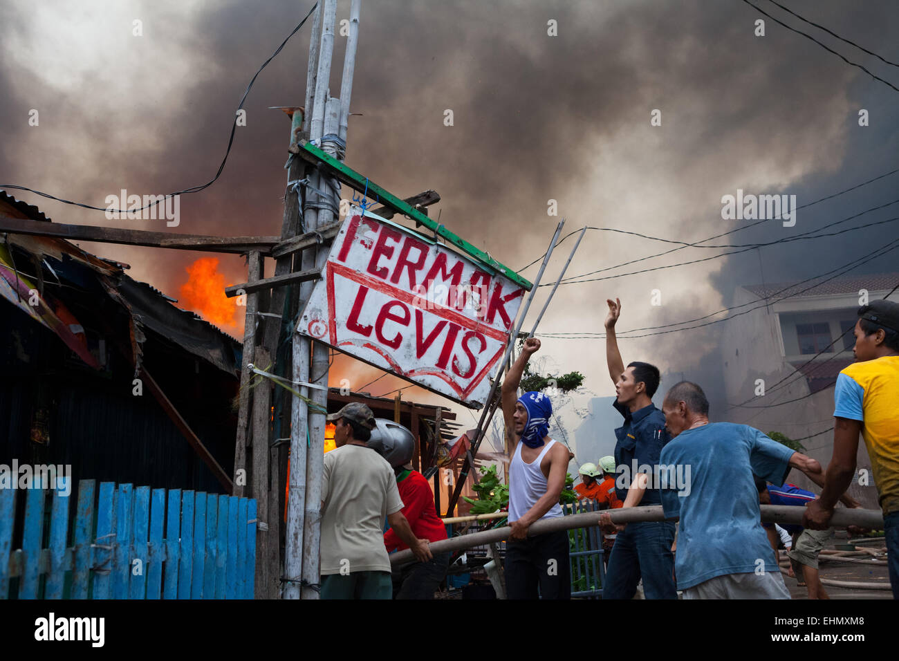 Local people coordinate to fight a fire accident in a densely populated area of Jakarta, Indonesia. © Reynold - Stock Image