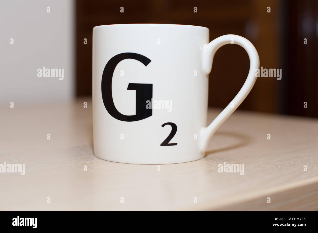 A Scrabble letter , a capital G with two points on a white mug  of tea or coffee during a work break on a table - Stock Image