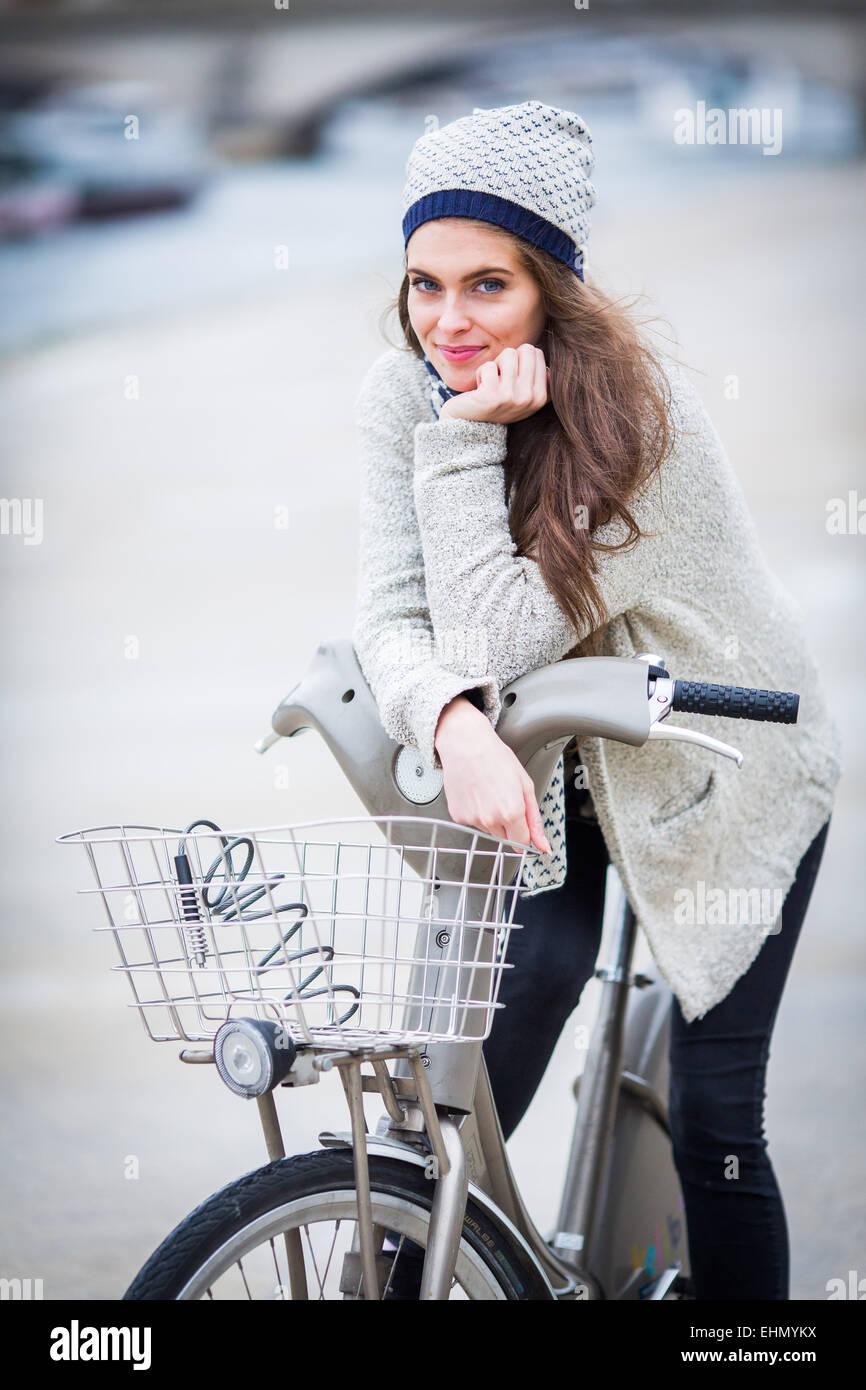 Woman using a Velib bike in Paris, France. - Stock Image