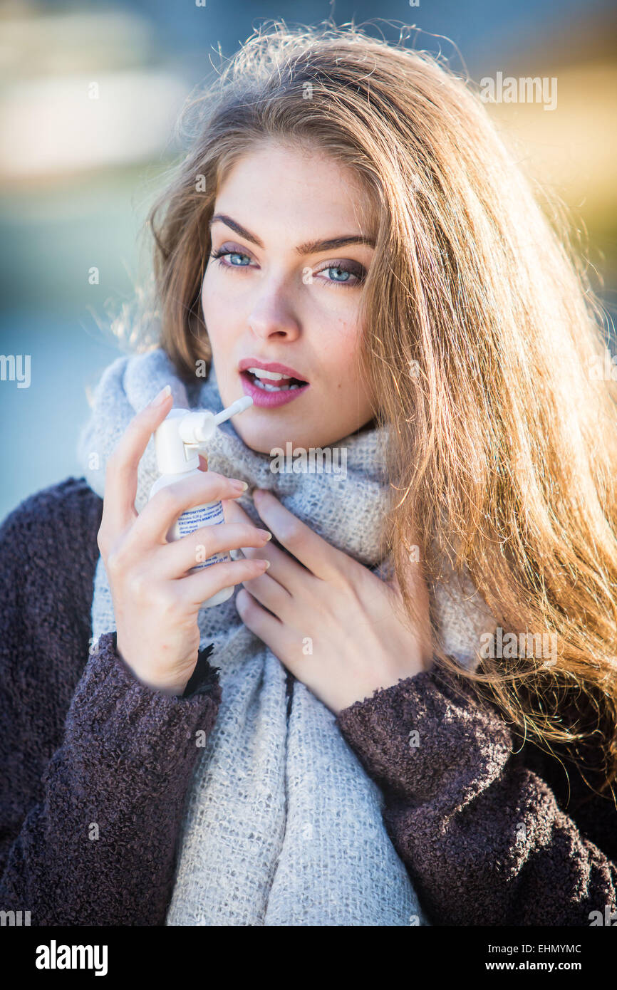 Woman using collutory spray for sorethroat. - Stock Image