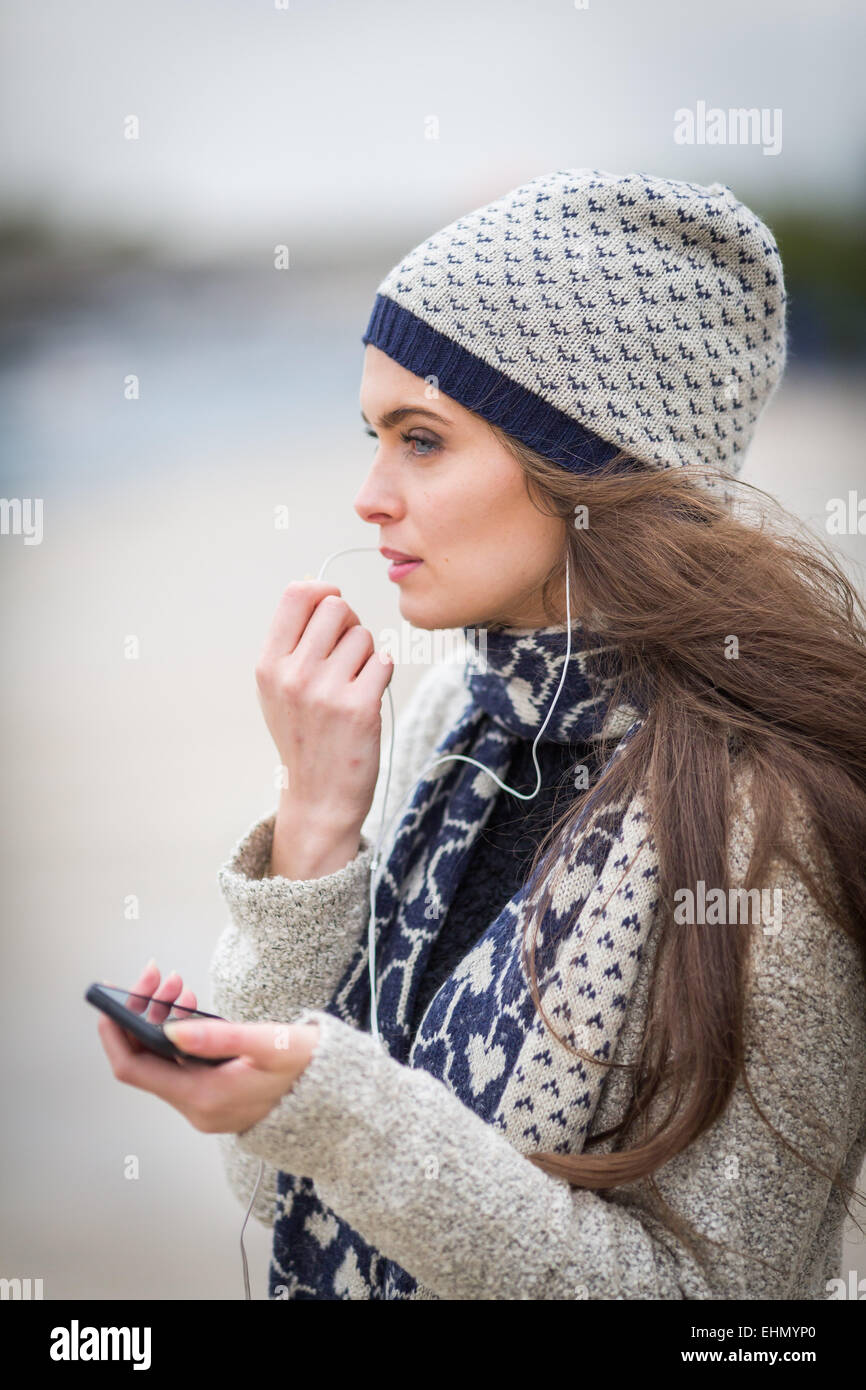 Woman using her cell phone with a hands-free kit. - Stock Image