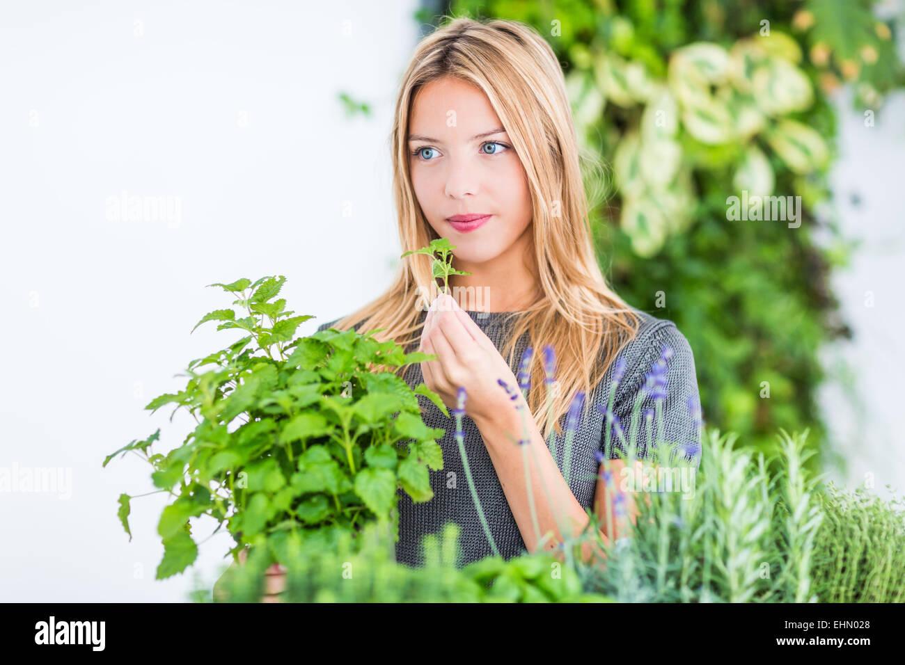 Woman inhaling lemon balm fragrance. - Stock Image