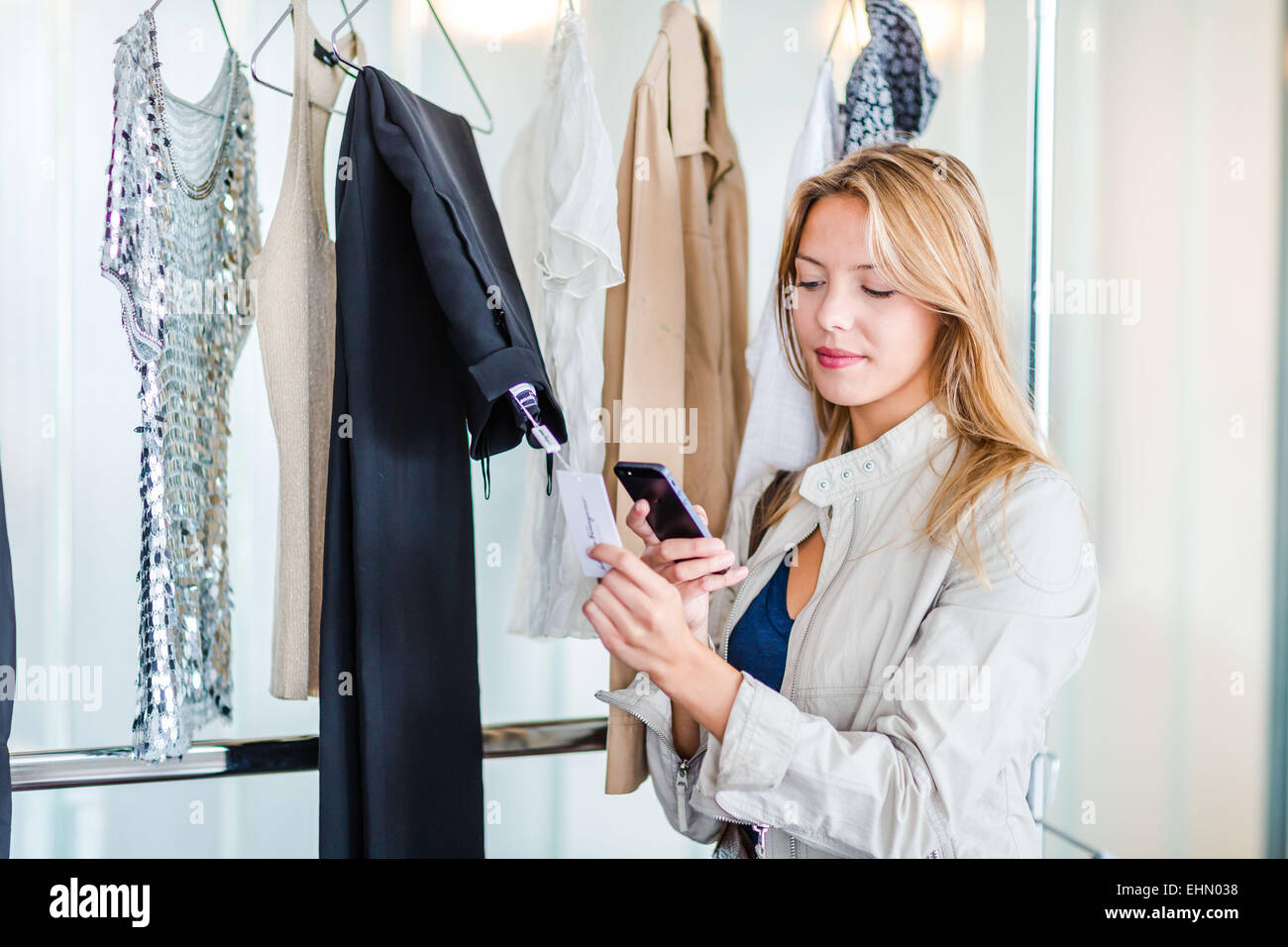 Woman using a smartphone in cloth shop. - Stock Image