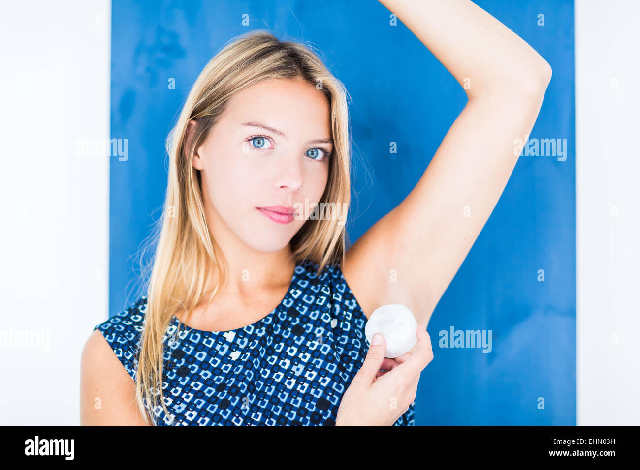 Woman using alumstone as deodorant. - Stock Image