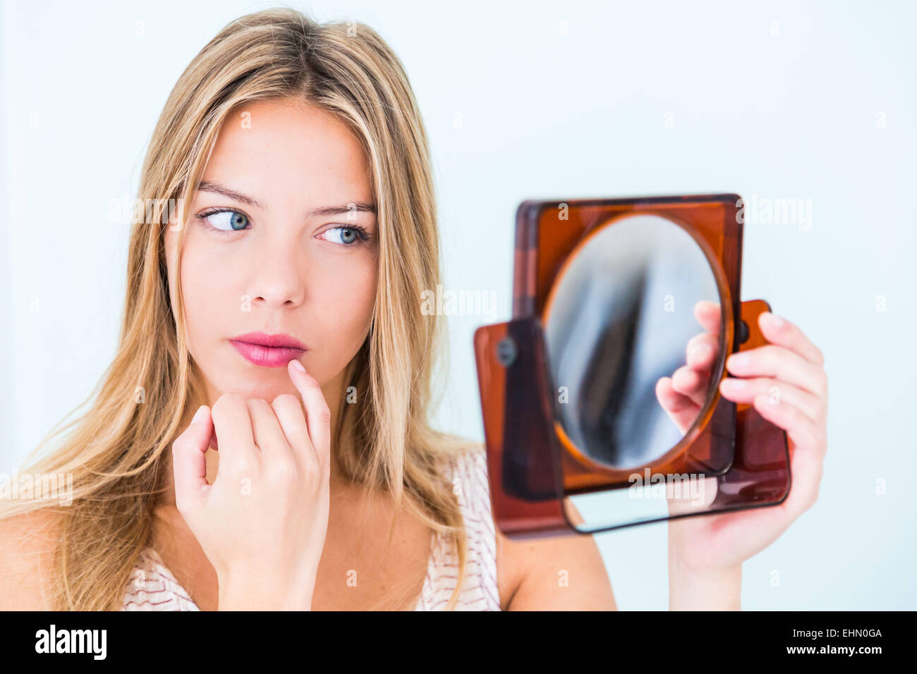 Young woman with finger on lips. - Stock Image