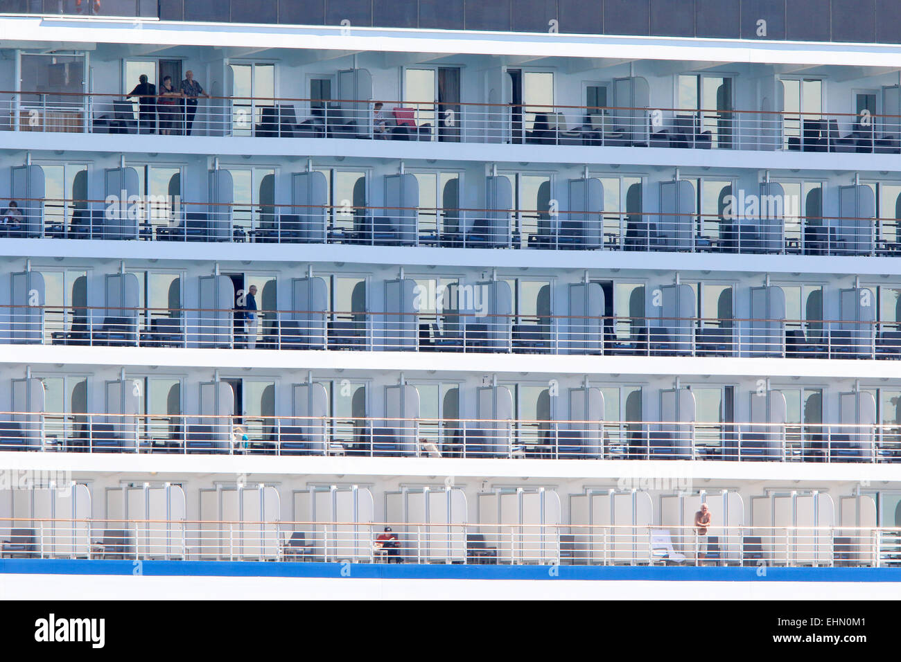 Cruise ship with passengers standing at balcony. - Stock Image