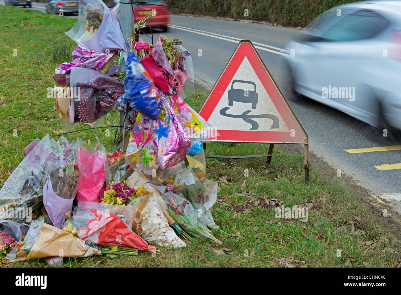 Cars speeding past a roadside shrine, the scene of a fatal accident - Stock Image