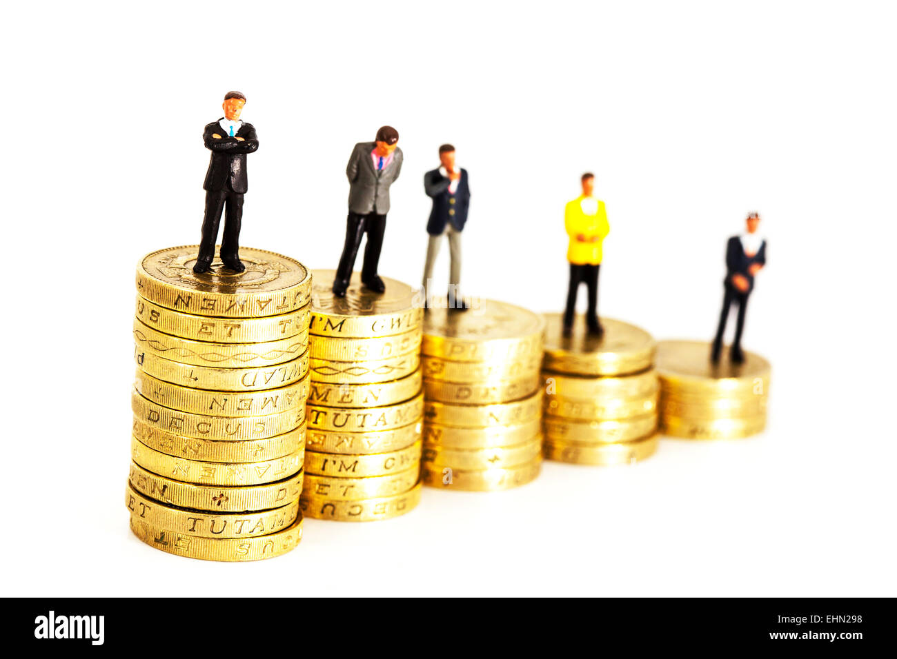 pay scale within business represented by pound coin stacks and businessmen isolated cut out cutout white background - Stock Image
