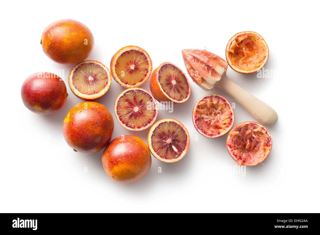 halved blood orange and juicer on white background - Stock Image