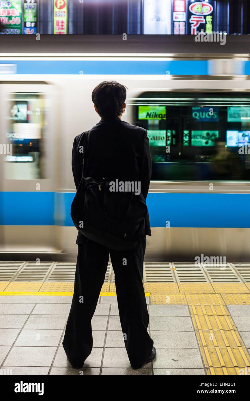 Businessmen in public transport, Tokyo, Japan. - Stock Image