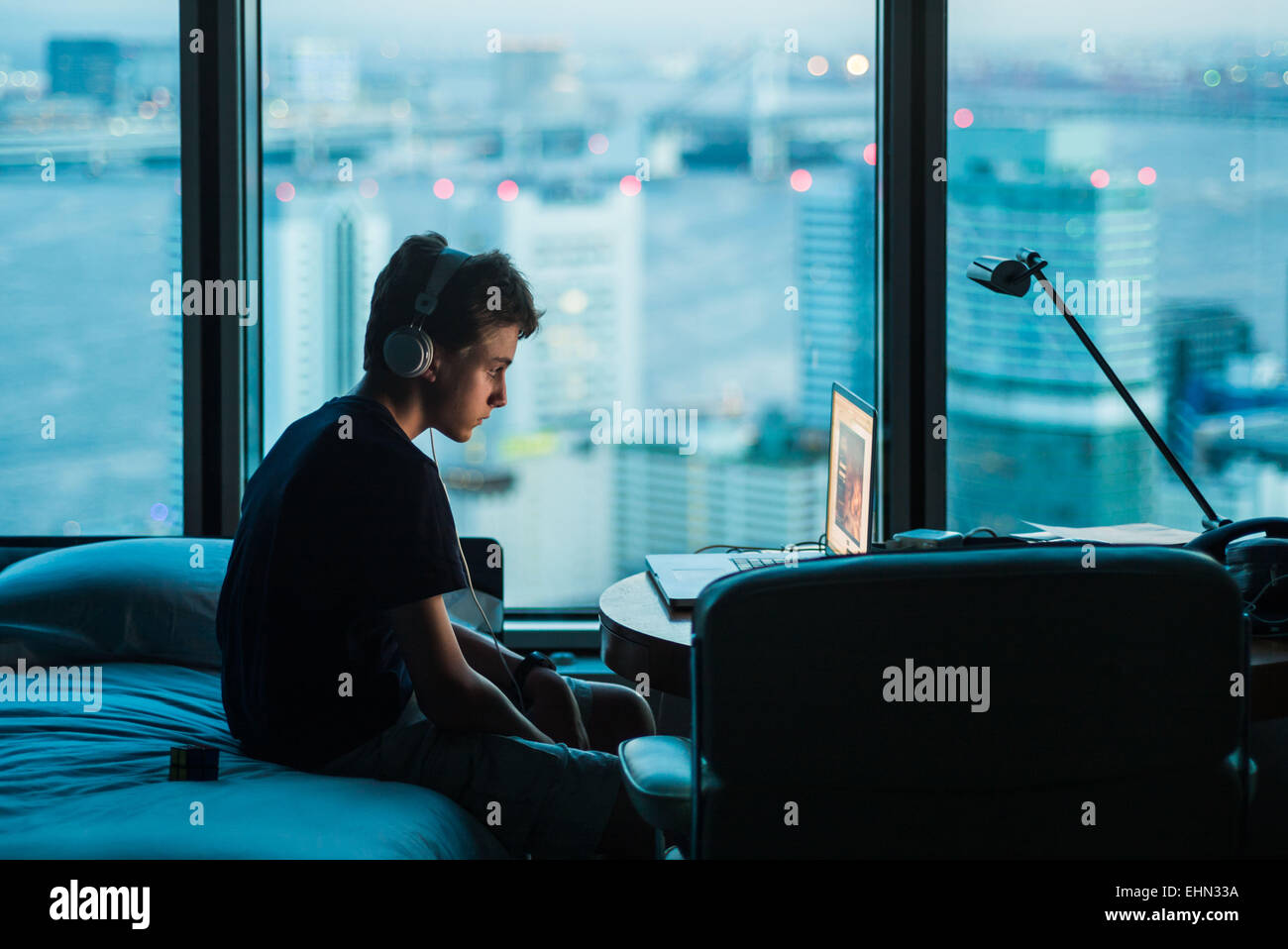 Teenage boy using a laptop. - Stock Image