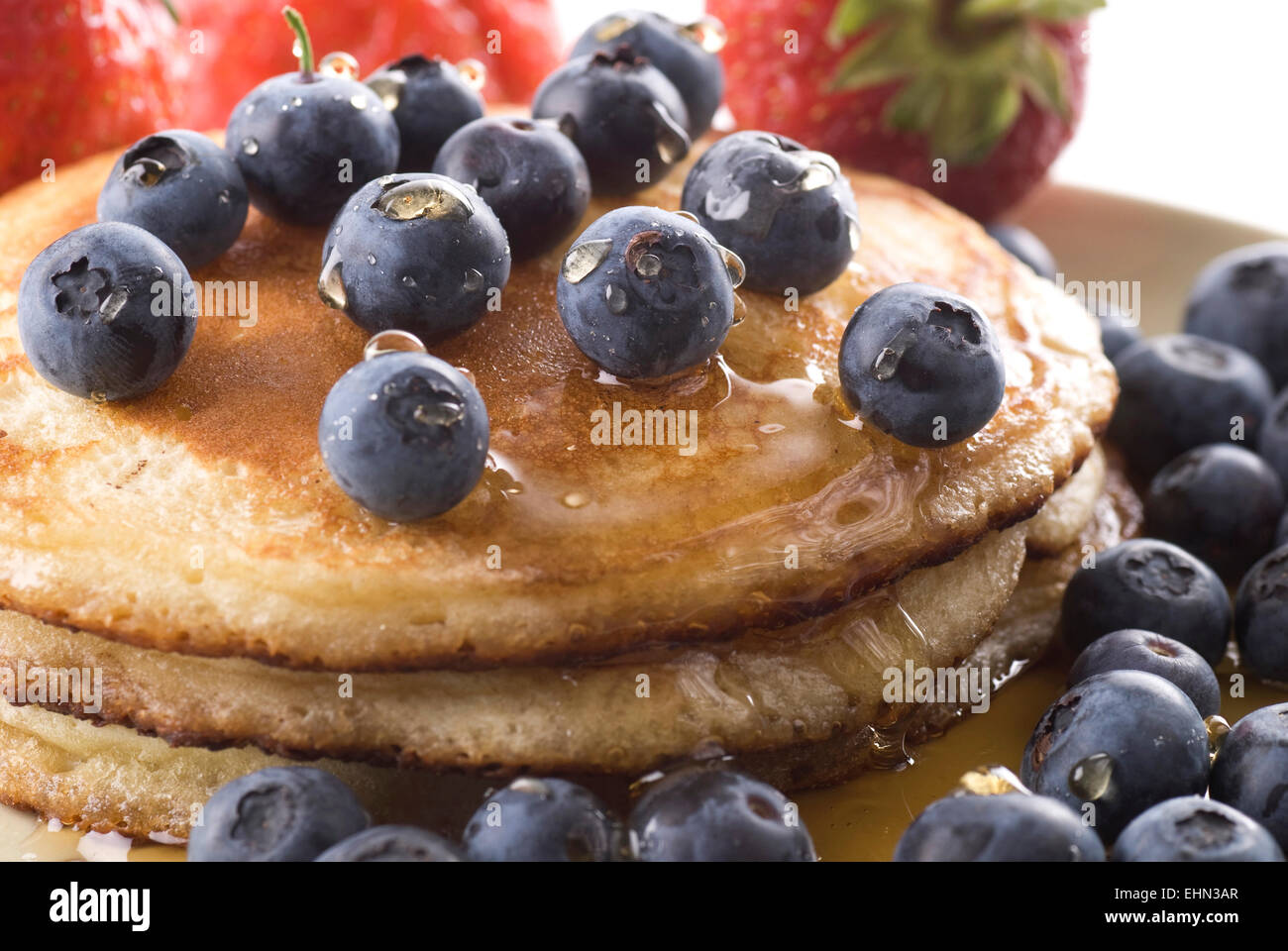 Pancakes with fresh blueberries and syrup on a plate.  Strawberries in the background. Stock Photo