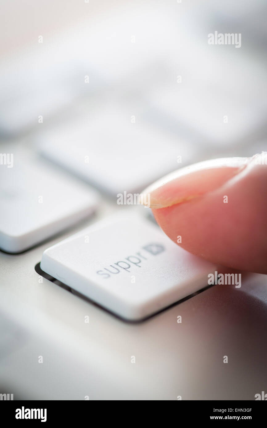 Woman pressing a button on a computer keyboard. - Stock Image