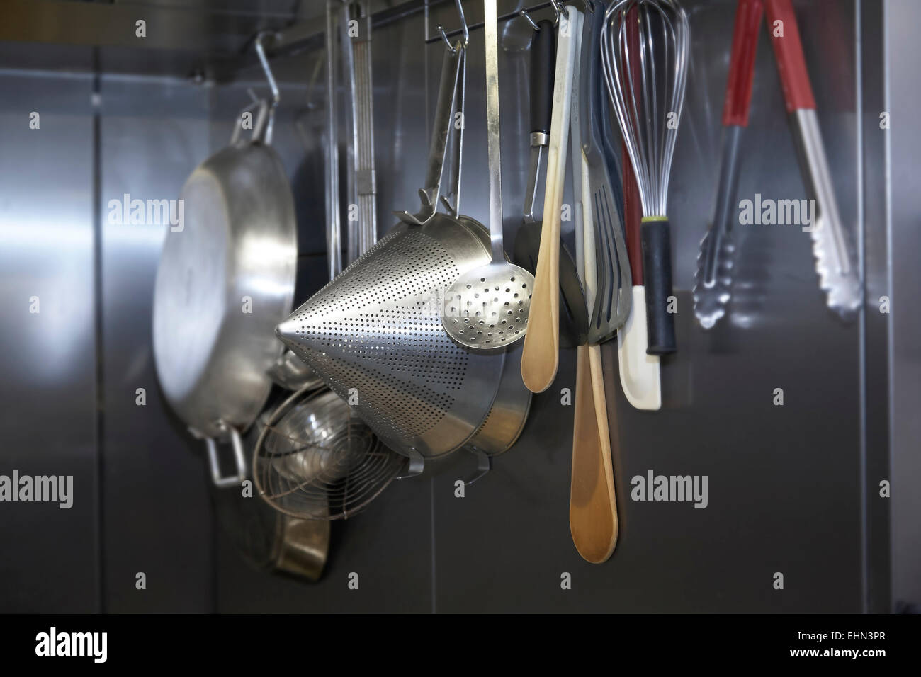 Utensils hanging up in a professional kitchen. - Stock Image