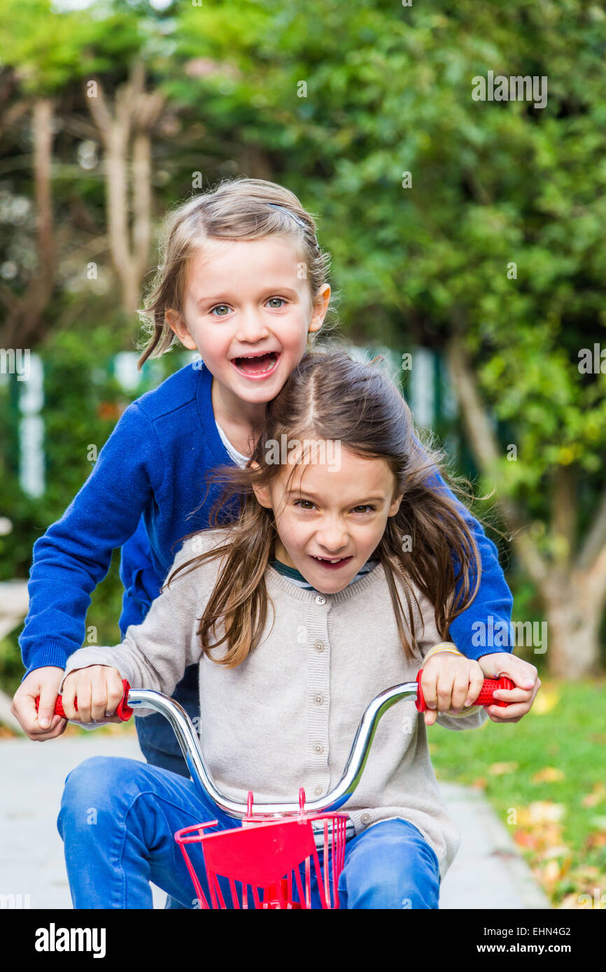 5 and 7 years old girls riding a bicycle. - Stock Image
