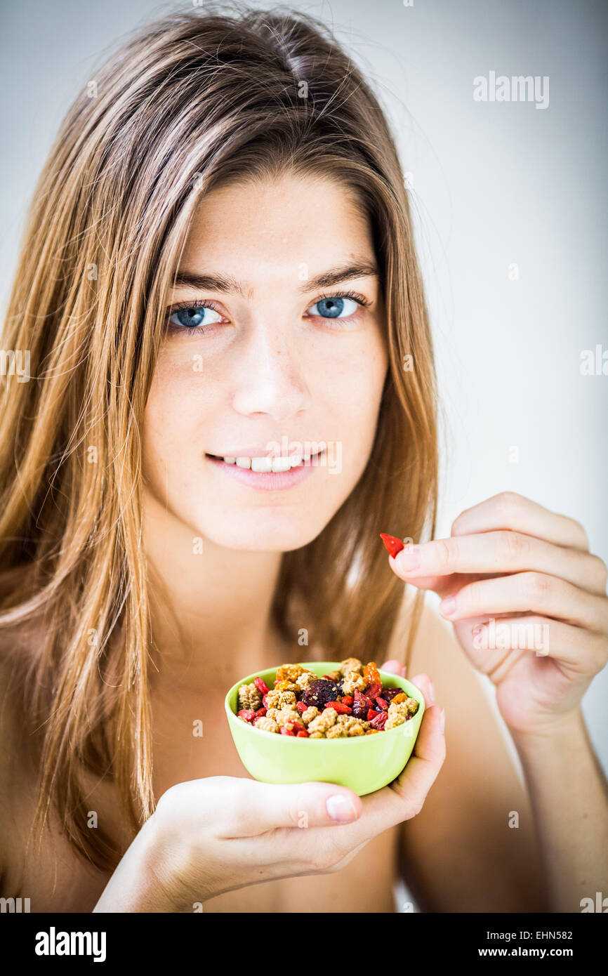 Woman eating several nuts. - Stock Image