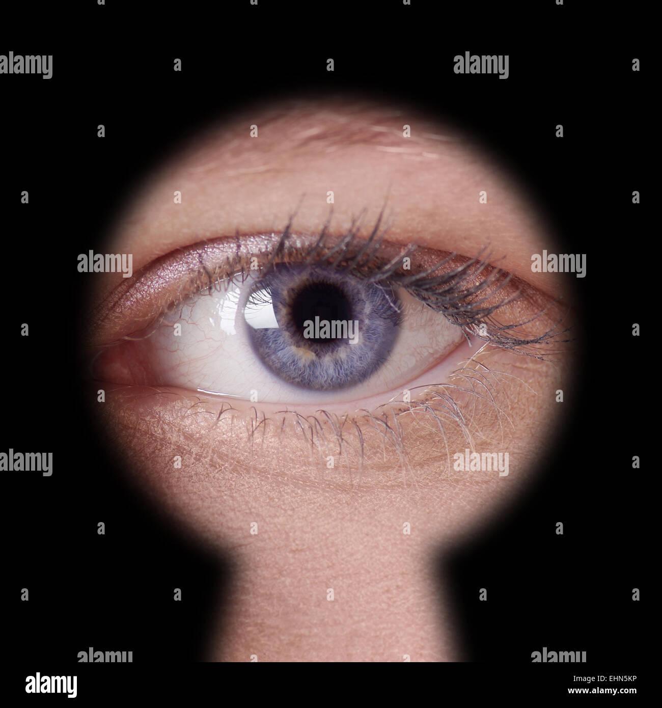 eye looking through keyhole - Stock Image