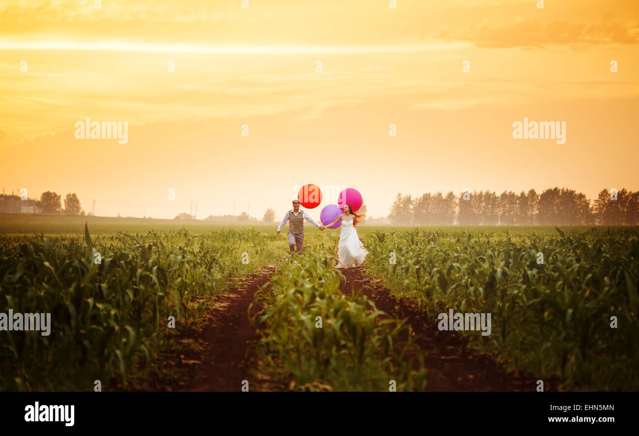 Happy young wedding couple running on the sunset field with big bright colorful balloons - Stock Image