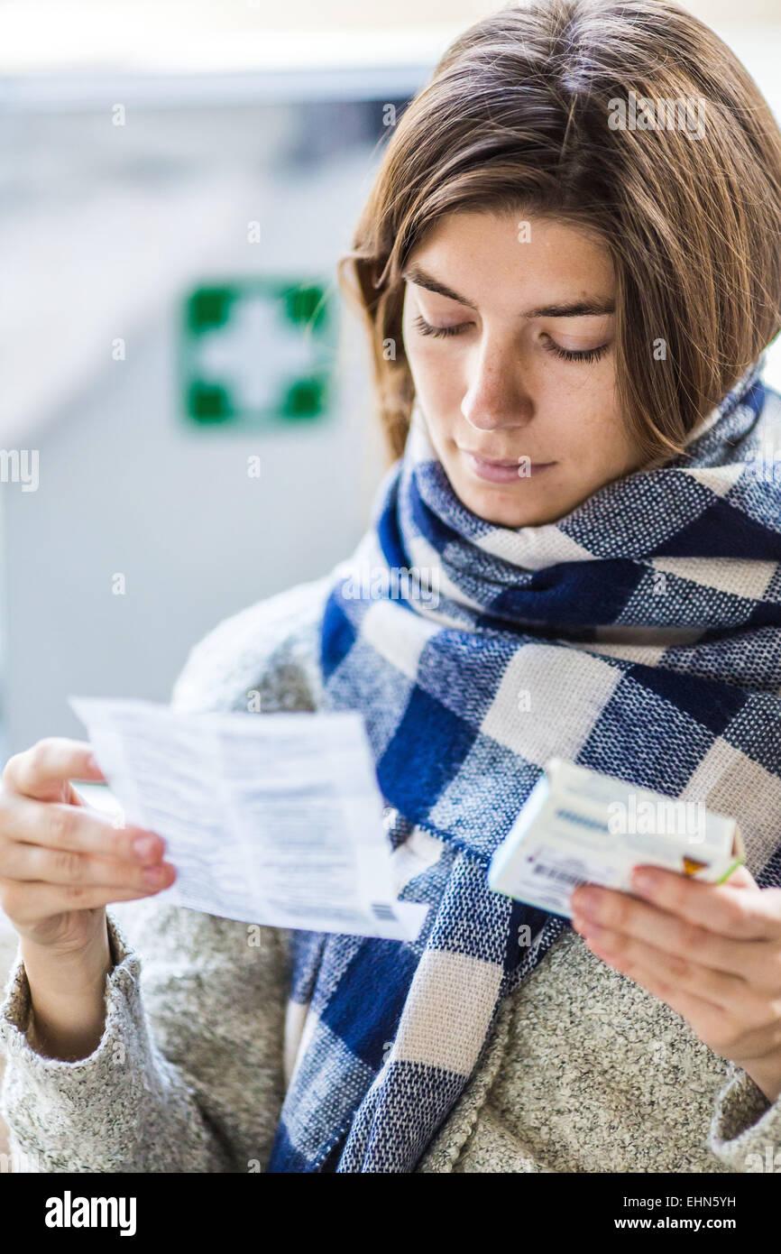 Woman reading medicine instruction sheet. - Stock Image