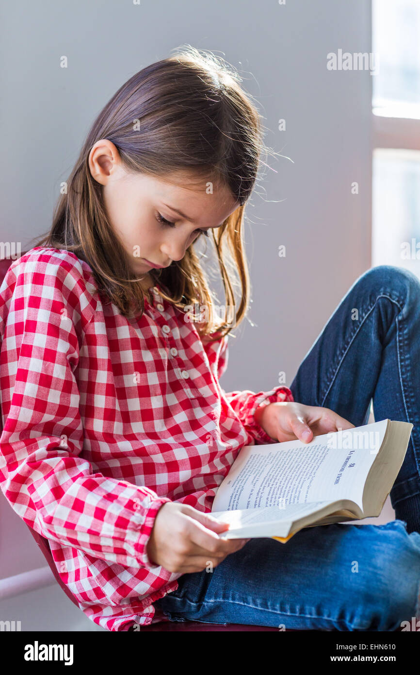 7 year old girl reading . - Stock Image