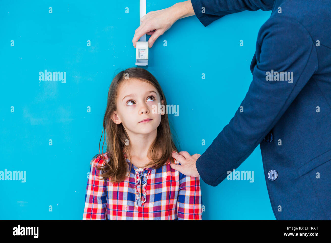 Doctor measuring the height of a young girl during a check-up. - Stock Image