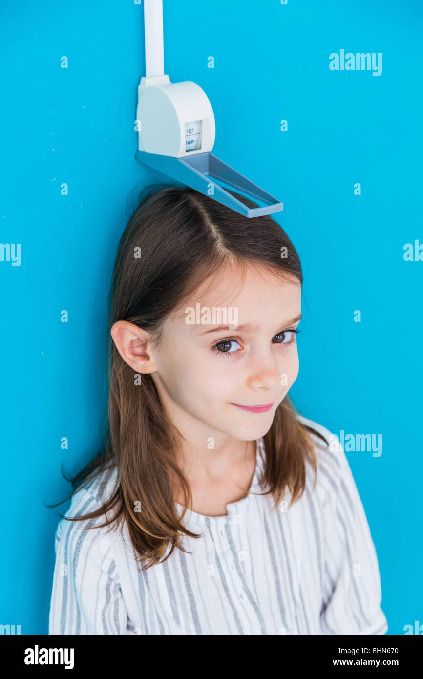 7-year-old girl measuring herself against a height gauge. - Stock Image