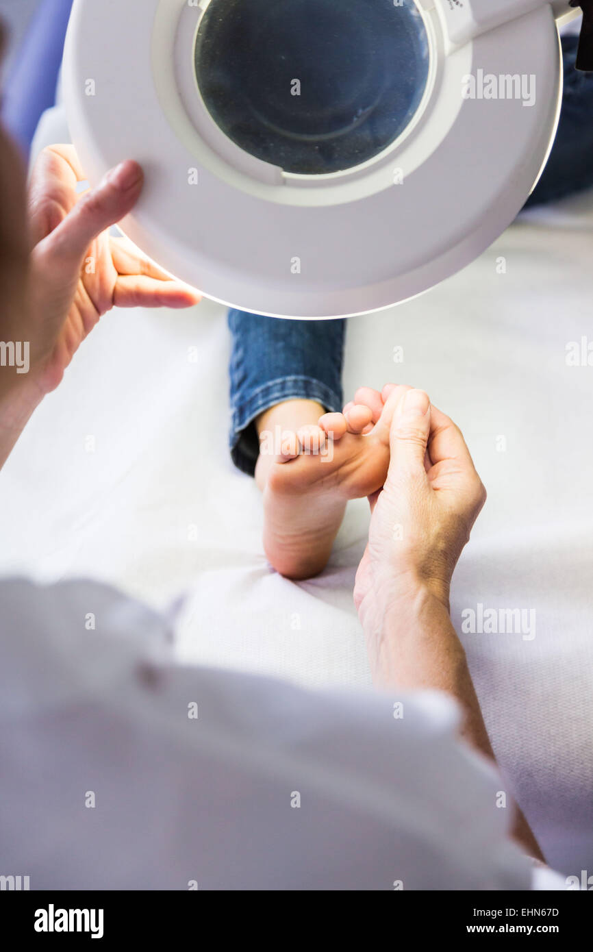 Doctor examining girl's foot. - Stock Image