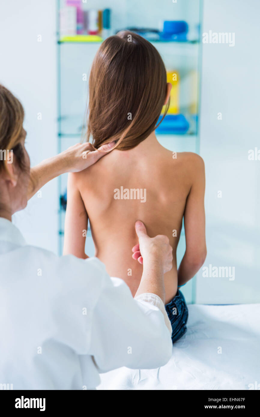 Doctor examining back of 7 year old girl. - Stock Image