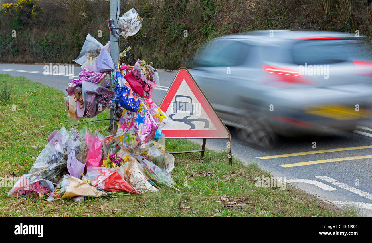 Car speeding past a roadside shrine, the scene of a fatal accident - Stock Image