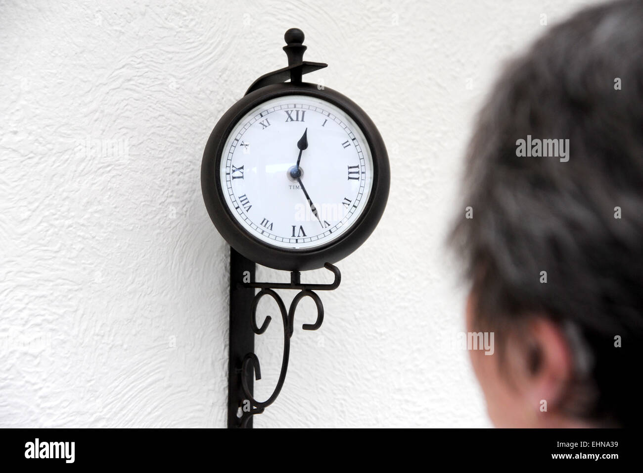 old lady female pensioner looking at clock on wall to tell the time