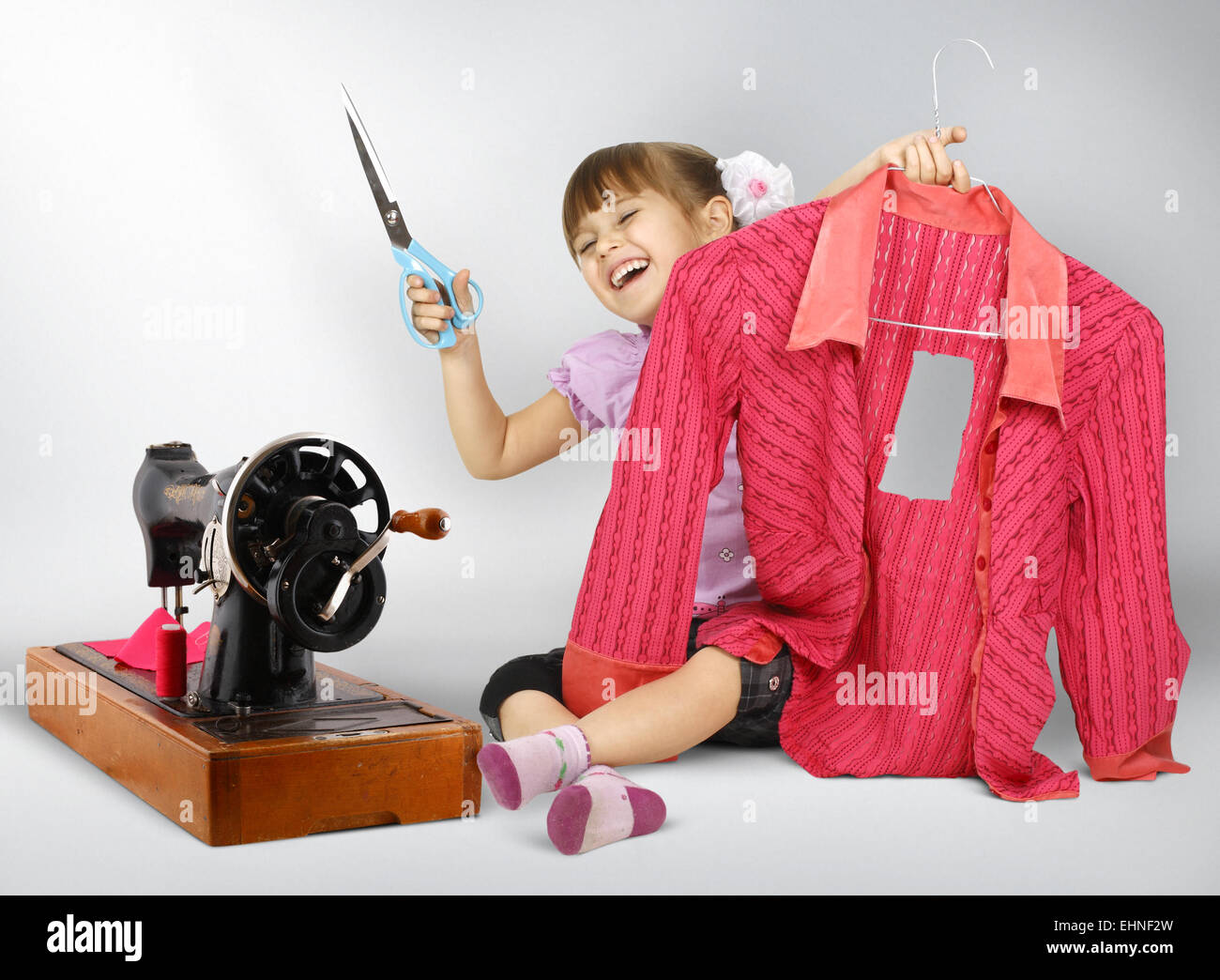 Little girl sewing , cuting dress - Stock Image