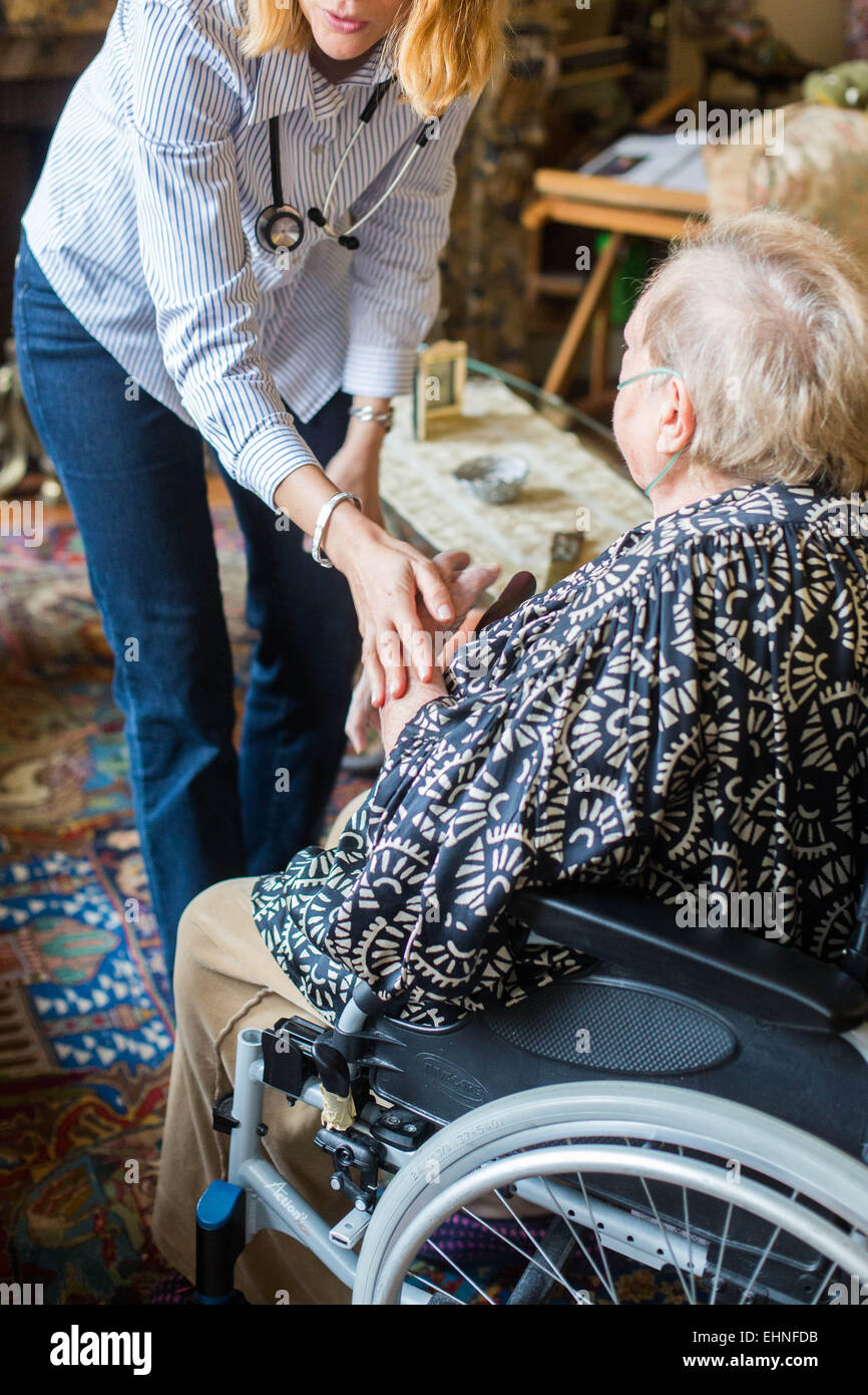 General practitioner on a home visit with an elderly patient. - Stock Image