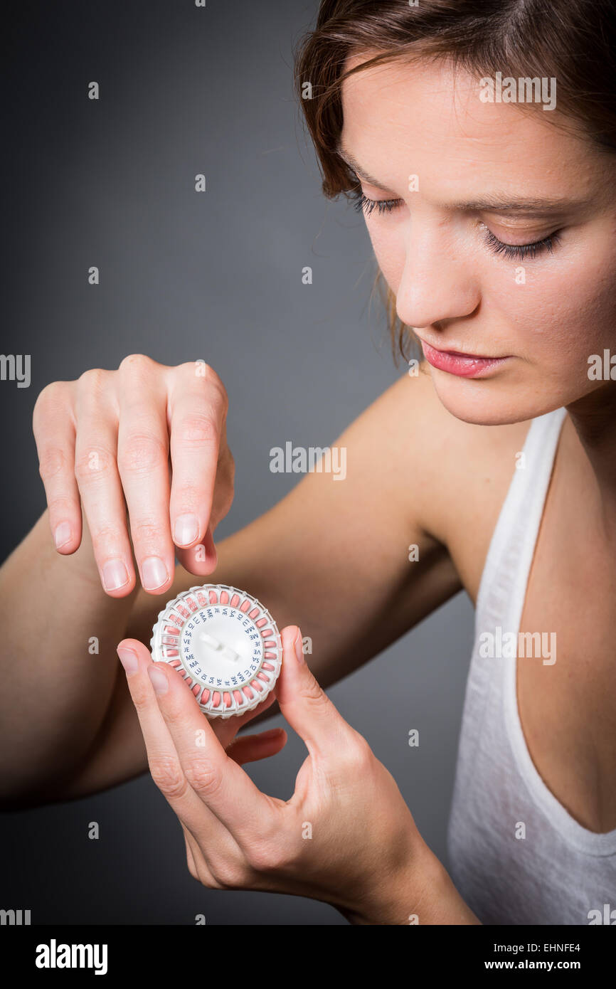 Woman taking an hormone replacement therapy pills. - Stock Image