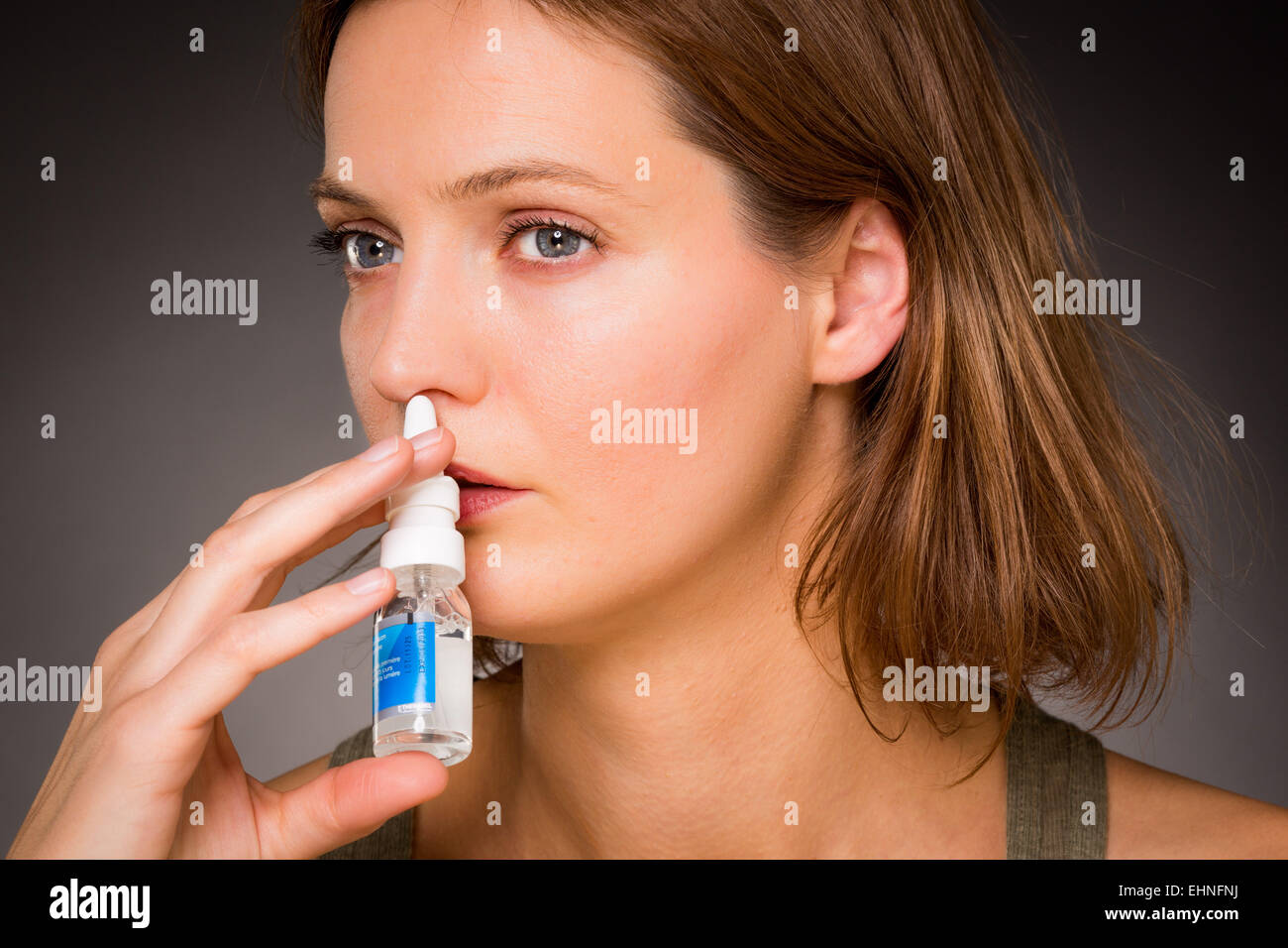 Woman using nasal spray for controlling rhinitis. - Stock Image