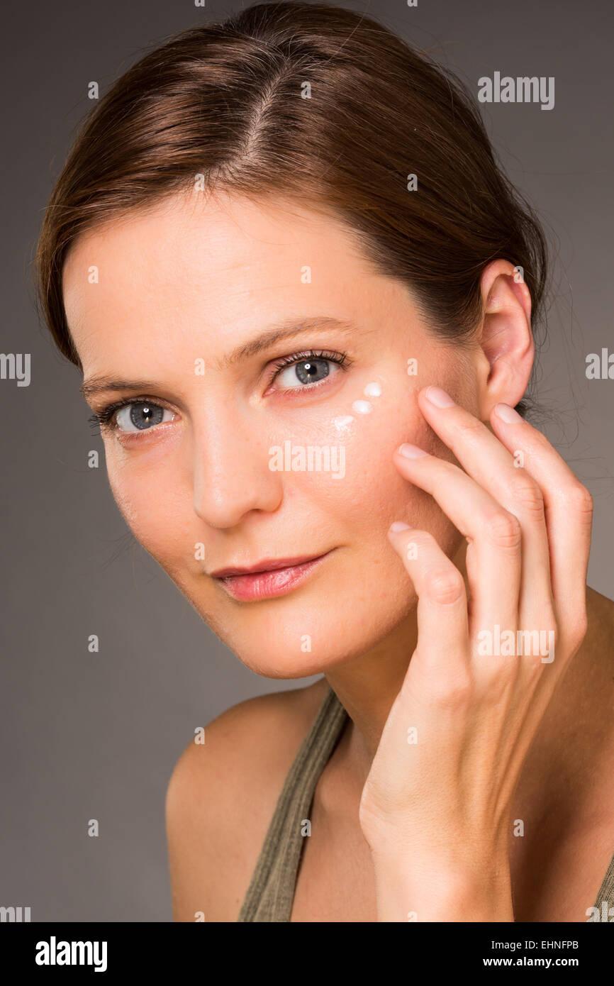 Woman applying anti-wrinkle cream around the eyes. - Stock Image