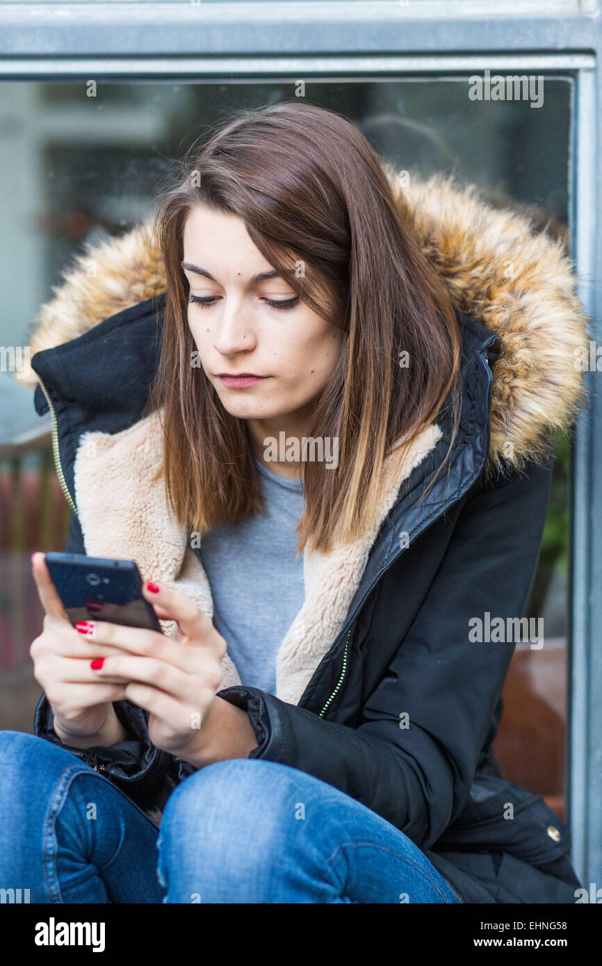 Woman using an Iphone®. - Stock Image