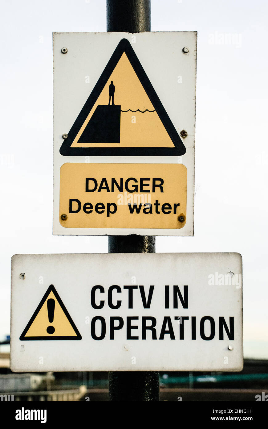 Signs at a harbour warning about deep water, and that CCTV is in operation Stock Photo