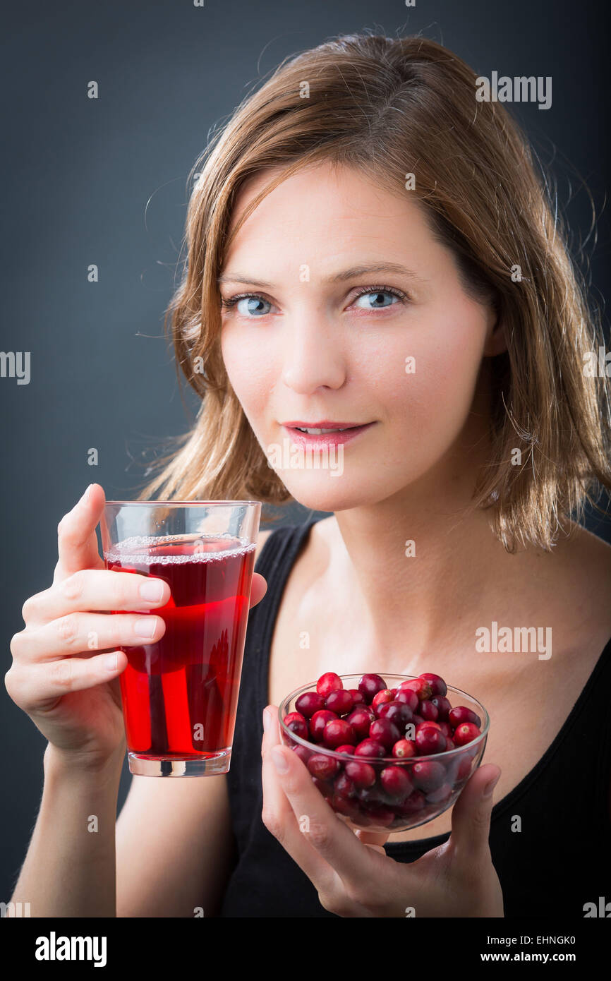 Woman drinking a glass of cranberry juice. - Stock Image