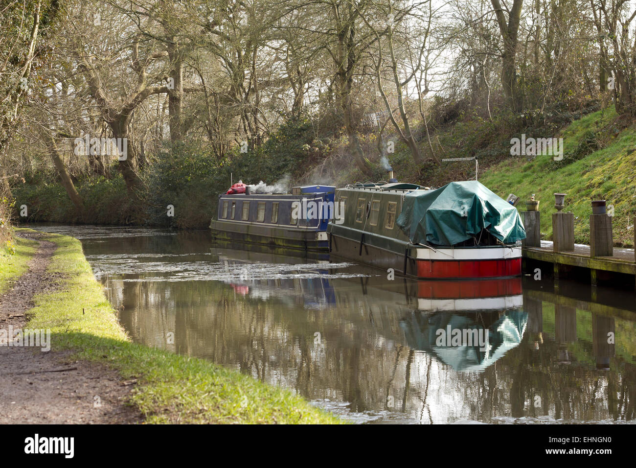Canal boats on a cold winter's day, with smoke coming from their chimneys, moored on a quiet country canal in - Stock Image
