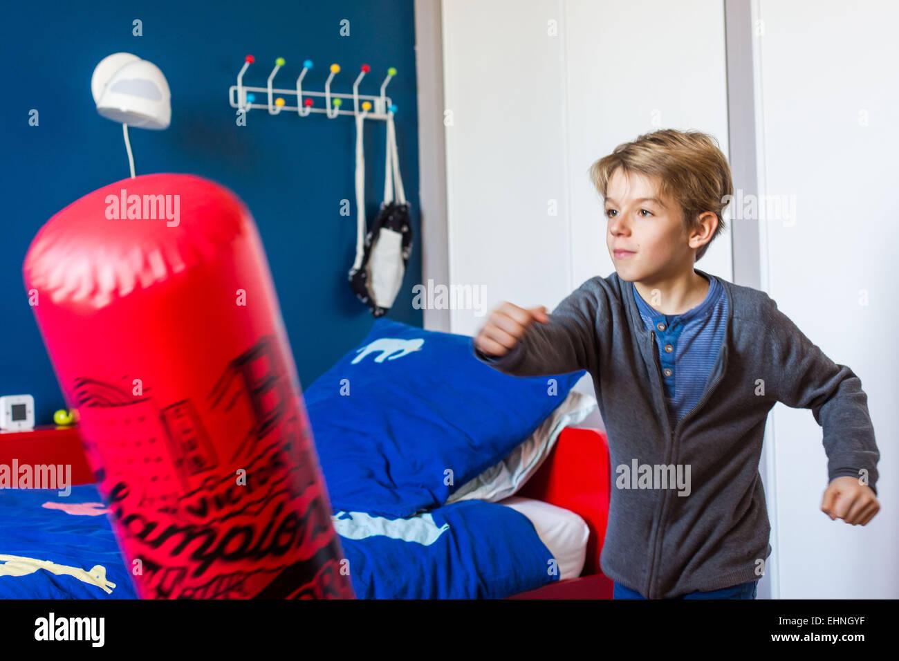 8 year old boy hitting a punching ball. - Stock Image