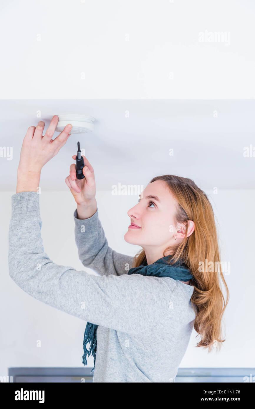 Woman installing a smoke detector. - Stock Image