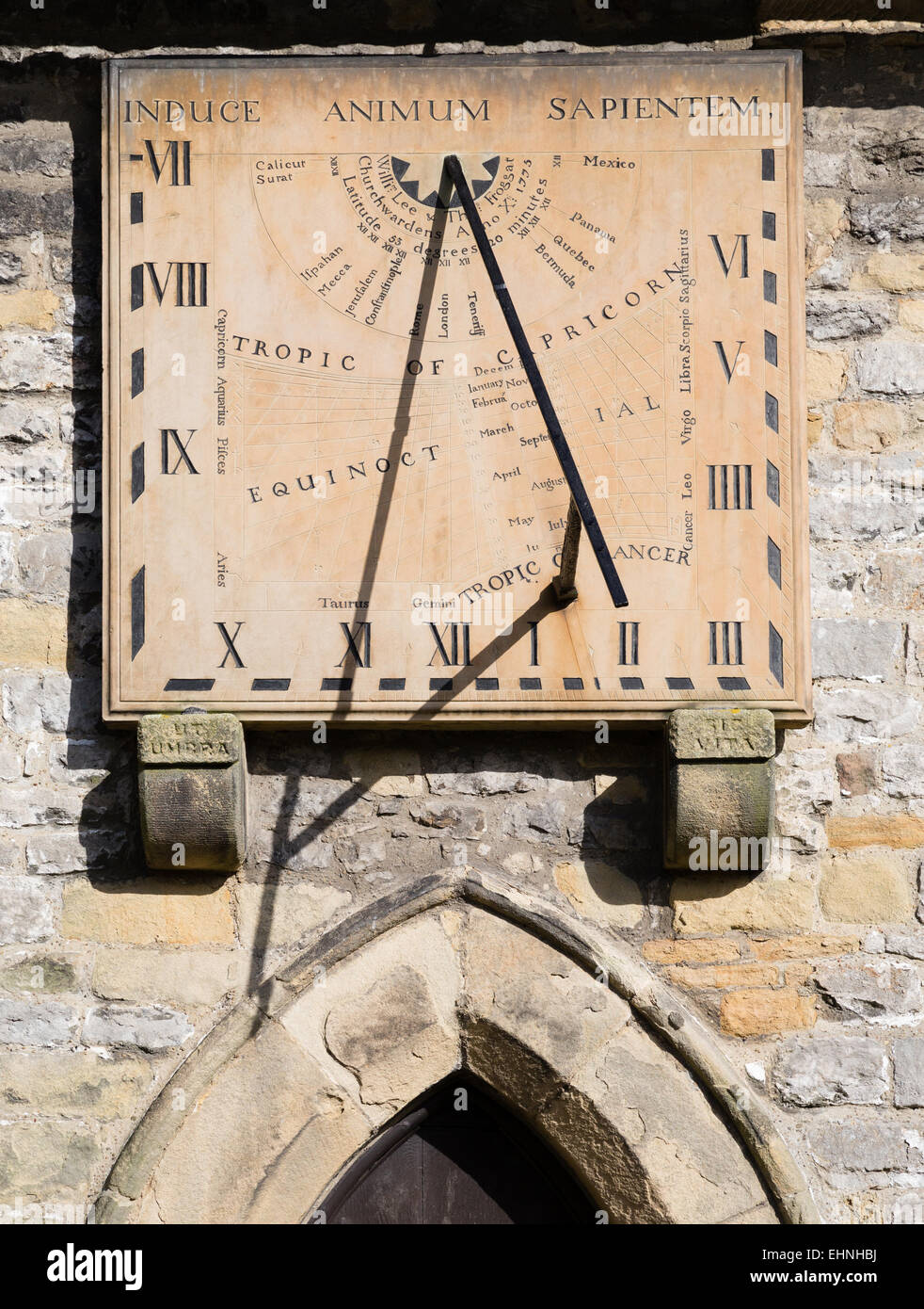 Sophisticated sundial above an entrance to St Lawrence's church in Eyam in the Derbyshire Peak District - Stock Image