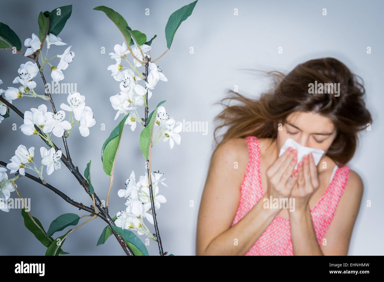 Woman with hay fever blowing her nose. - Stock Image