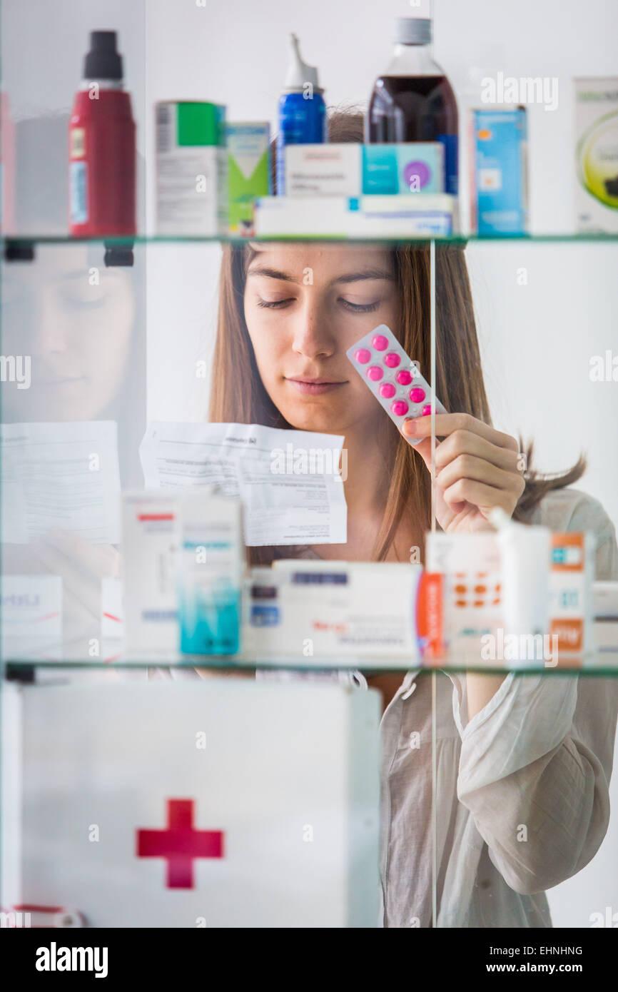 Woman reading medicine instruction sheet. Stock Photo