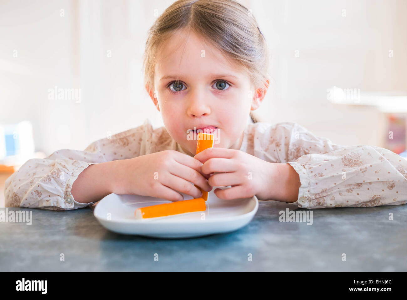5 year-old girl eating surimi. - Stock Image