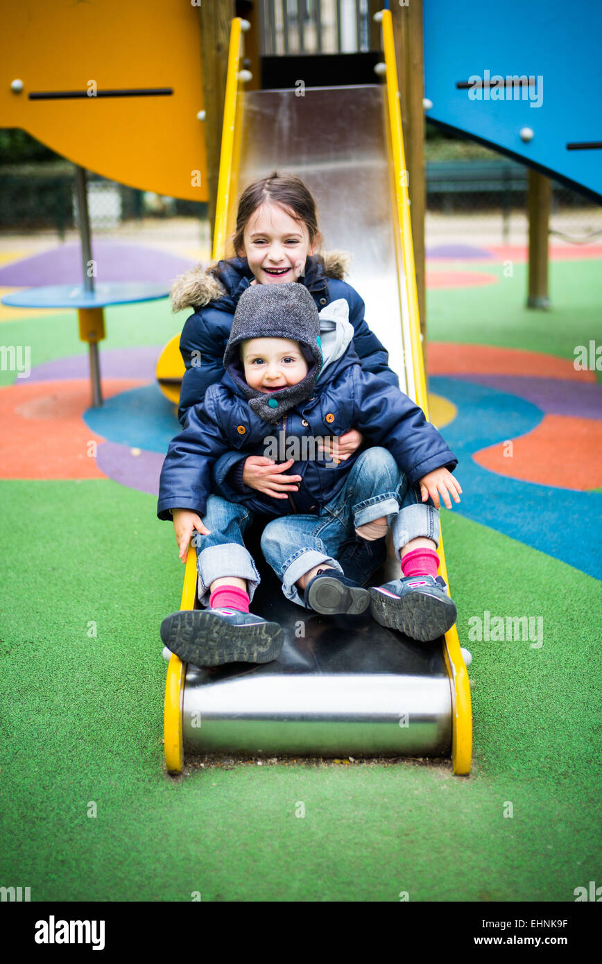 7 year-old girl and 18 month-old baby boy on a slide in a playground. - Stock Image