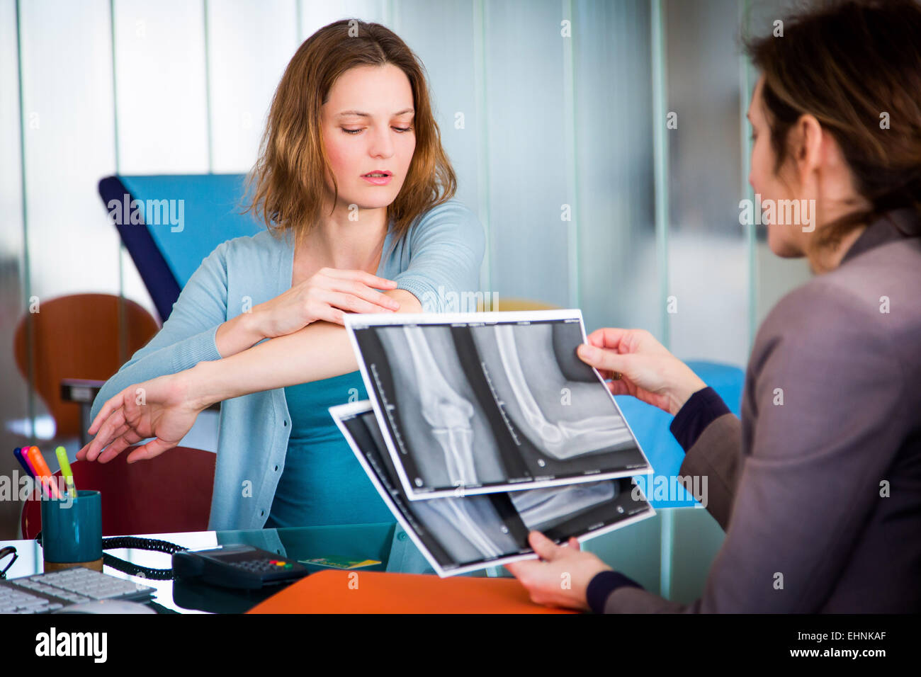 Doctor examining and commenting patient's elbow X-ray. - Stock Image