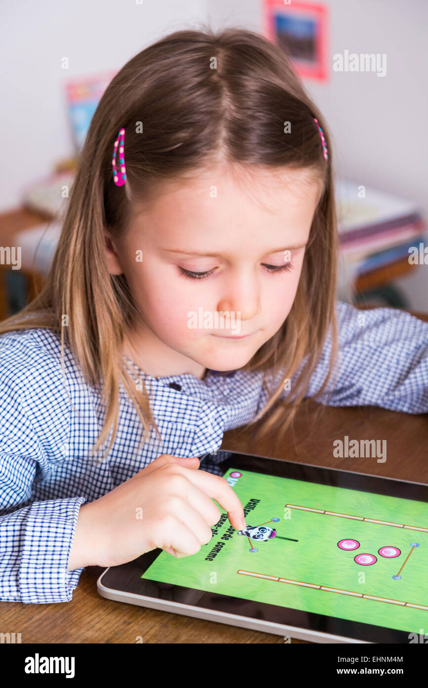 5 year-old girl using tablet computer. - Stock Image